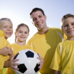 Coach with young players and soccer ball